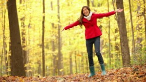 stock-footage-fall-woman-happy-throwing-autumn-leaves-having-fun-laughing-in-beautiful-colorful-forest-foliage